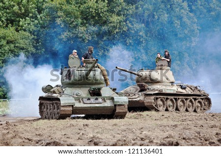 BELTRING, UK - JULY 19: Two T34 ex Russian army tanks give a fire and maneuver demonstration to the public in the main viewing arena at the War & Peace show on July 19, 2012 in Beltring - stock photo