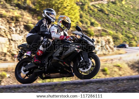 BEMBIBRE, SPAIN - JUNE 23: Motorcyclist and passenger unidentified with Kawasaki Ninja ZX-RR 600 in the 3rd motorcycle rally Bierzorros in Bembibre (Leon) on June 23, 2012 in Bembibre, Spain. - stock photo