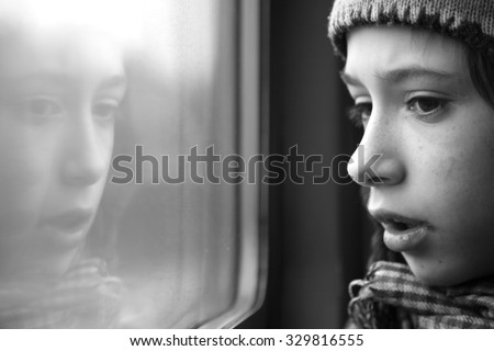 Bemused face of a boy with his reflection in the window