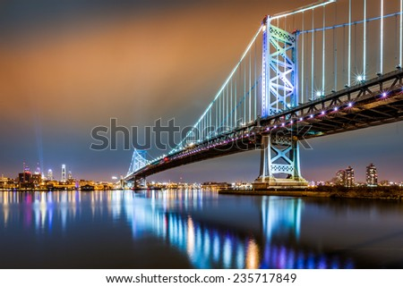 Ben Franklin Bridge and Philadelphia skyline by night as viewed from Camden, across the Delaware river - stock photo