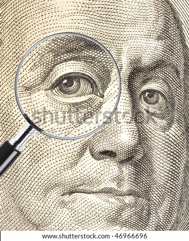 Ben Franklin dollar image with eye enlarged by a magnifying glass - stock photo