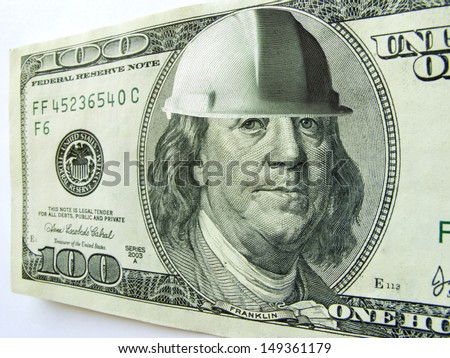 Ben Franklin wears a hard hat on this one hundred dollar bill which might illustrate the cost of construction or safety in a business or industrial environment. - stock photo