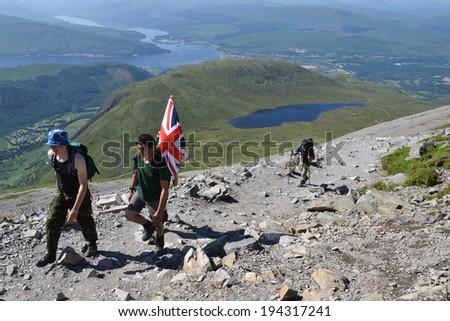 BEN NEVIS, UNITED KINGDOM - JULY 19: People hiking on the Ben Nevis summit on 19 July 2013 in Fort William, Scotland, UK. - stock photo