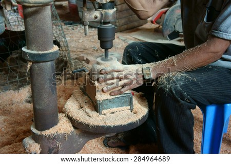 BEN TRE, VIET NAM- JUNE 2: Asian worker working at wood workshop, Vietnamese people make product from coconut tree trunk, tradition craft,  in polluted enviroment, Mekong Delta, Vietnam, June 2, 2015