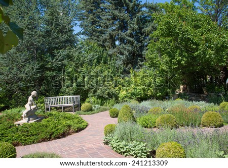 Bench and walkway in a green park - stock photo