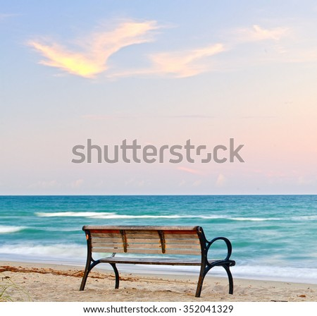 Bench by the beach at sunset in Florida - stock photo
