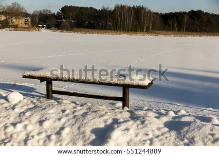 bench covered with snow on the shore of a frozen lake