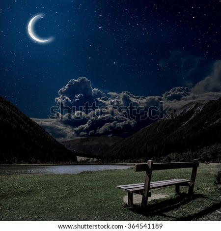 bench for relaxing with a view on the night Alps in Austria. Elements of this image furnished by NASA - stock photo