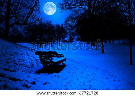 Bench in a park covered in snow at midnight with a bright full moon - stock photo