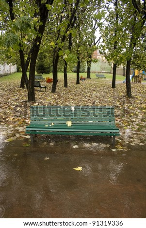 Bench in autumn under rain - stock photo