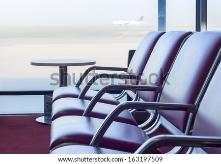 Bench in departure flights waiting hall at the airport with airplane in the background - stock photo