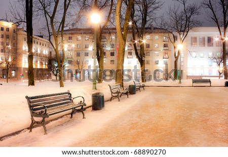 Bench in evening winter city - stock photo