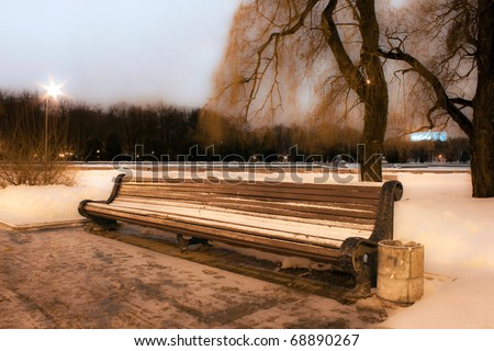 Bench in evening winter park. - stock photo