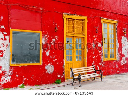 Bench in frond of an old red restaurant in the small port kamini of island Hydra in Saronikos gulf in Greece - stock photo