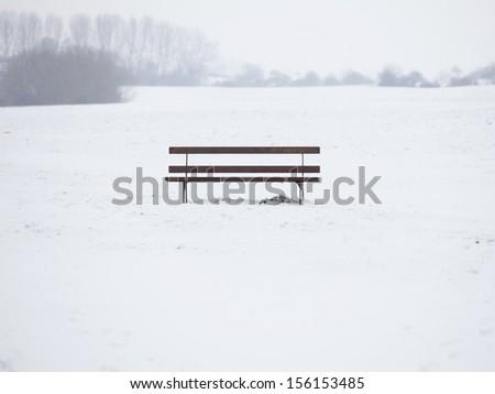 Bench in the middle of snow - stock photo