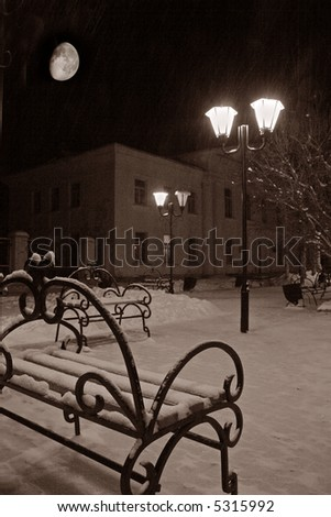 bench in the night under moon in winter