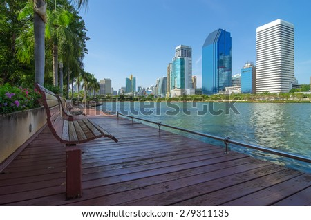 Bench in the park along the lake. The building has a modern foreground.