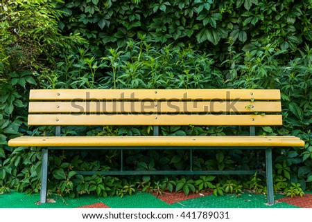 Bench in the park on a background of vegetation. Bench on the protective coating - stock photo