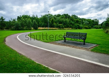 Bench in the park with footpath - stock photo
