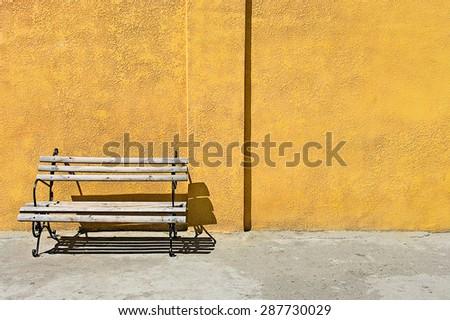 bench near Grunge aged texture street urban background yellow wall saver model shooting - stock photo