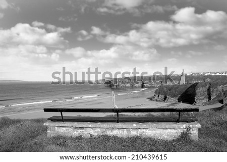 bench on a cliff edge  with views of Ballybunion beach cliffs and castle in black & white - stock photo