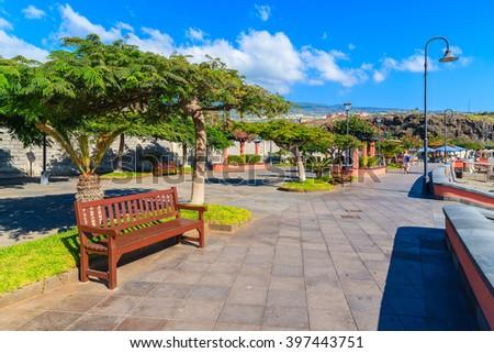 Bench on coastal promenade along a tropical beach in San Juan town on Tenerife, Canary Islands, Spain - stock photo