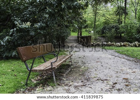 bench on dirt track  soaked by the rain in the Retiro Park. Madrid,Spain