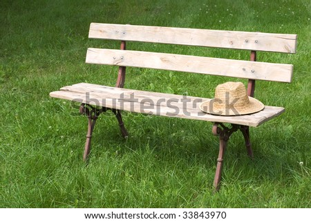 bench on grass with hat