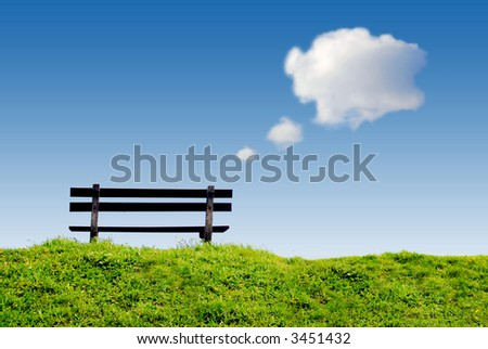 bench on green grass with conceptual text-balloon thinking and day dreaming clouds in clear blue sky - stock photo
