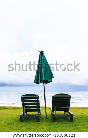 Bench on green grasses on seashore in the morning in Phang nga province , Thailand - stock photo