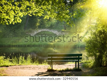 Bench on the bank of the river in summer day - stock photo