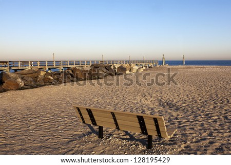 Bench on the Beach. Empty bench and Jetty directing toward the ocean, Ceder Beach. Long Island, New York - stock photo