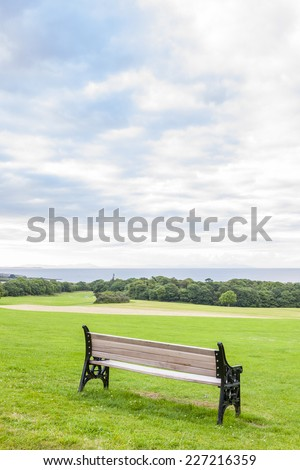 Bench on the green grass in the park looking at the sea - stock photo