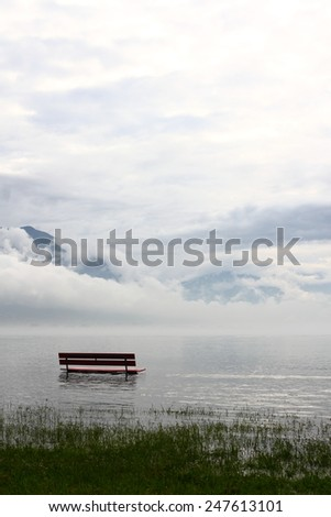 Bench on the lake shore during a flooding - stock photo