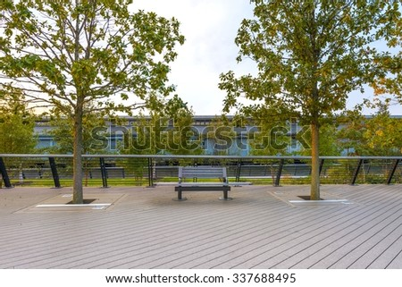 bench on tree lined Ben Franklin Bridge public walkway and building with loading bays across the river - stock photo