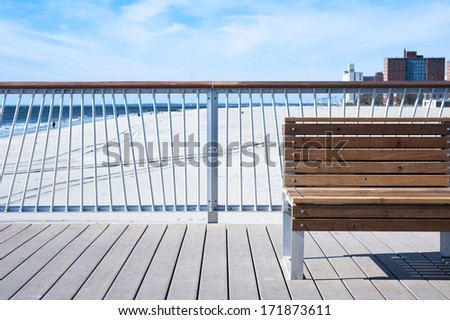 Bench on wooden Pier at seaside and beautiful blue sky and clouds in the background - stock photo