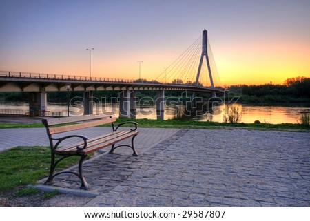 bench over Vistula river at sunrise, near Swietokrzyski bridge, Warsaw, Poland - stock photo