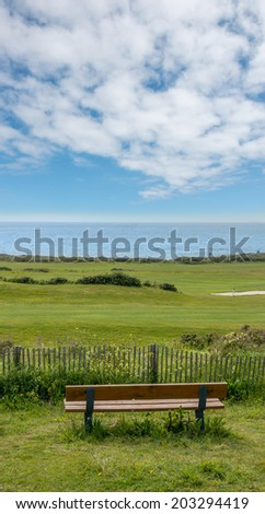 Bench overlooking green fields and the ocean - stock photo