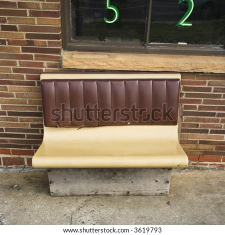 Bench seat outside brick building. - stock photo