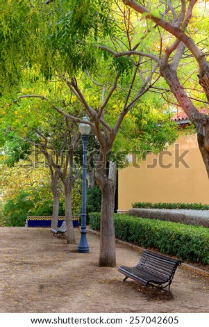 Bench under the tree in the gardens in Barselona - stock photo