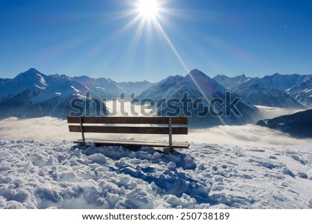 Bench with view over the winter Alps - stock photo