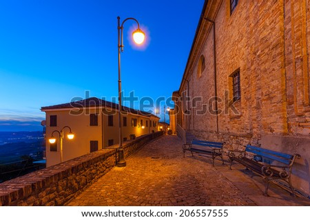Benches on narrow illuminated cobbled street early in the morning in small italian town. - stock photo