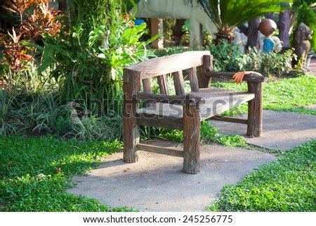 Benches on the walkway in the park on the grass. Decorated with trees and shrubs in the garden. - stock photo