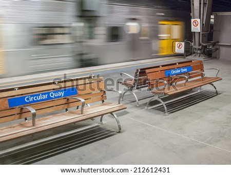 Benches with moving train in Circular Quay subway station, Sydney - Australia. - stock photo
