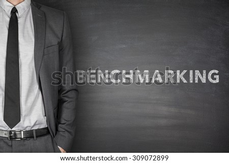 Benchmarking text on black blackboard with businessman - stock photo