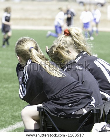 Benchwarmers watching soccer game - stock photo