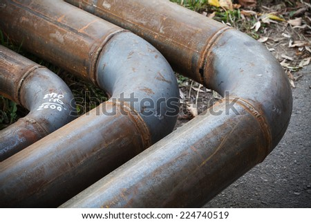 Bend of industrial steel pipeline over asphalt urban road - stock photo