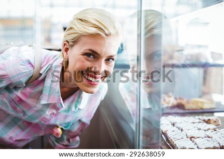 Bended pretty woman looking at the camera at the bakery - stock photo