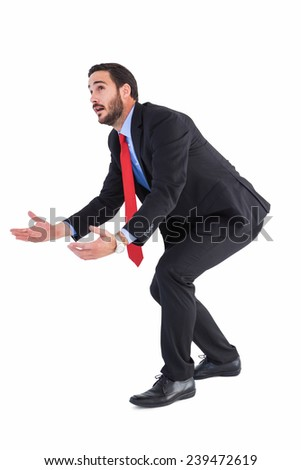 Bending businessman holding hand out while looking up on white background