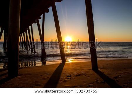 Beneath the Virginia Beach fishing pier at sunrise - stock photo